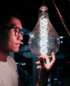 Photo of man looking at inventive light bulb